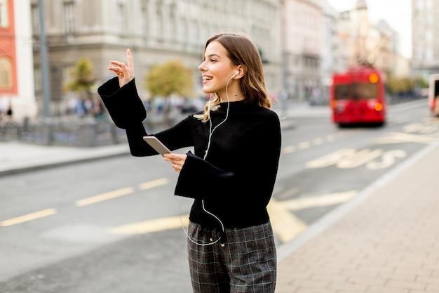 Молодая женщина, ожидающих такси или автобуса на улице в городе
