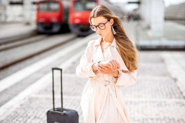 Молодая женщина ждет поезд, грустно стоящий на платформе на железнодорожном вокзале