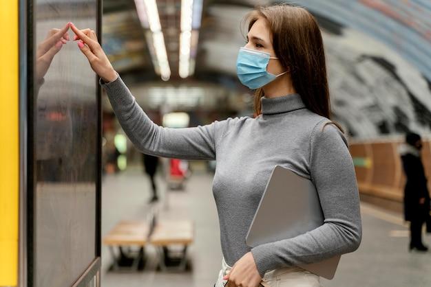 Молодая женщина ждет на станции метро с планшетом