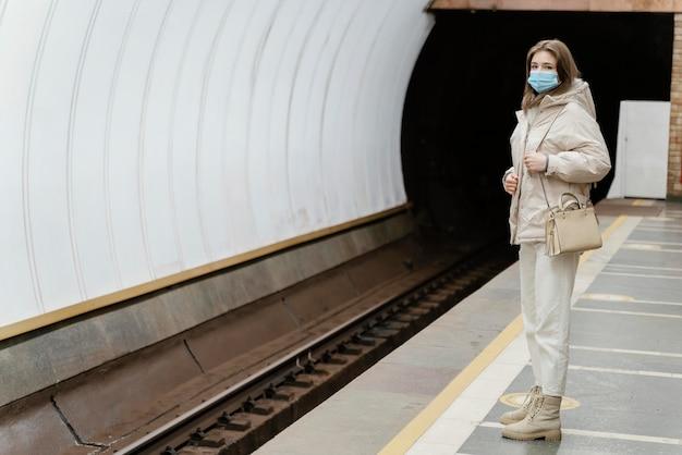 地下鉄の駅で待っている若い女性