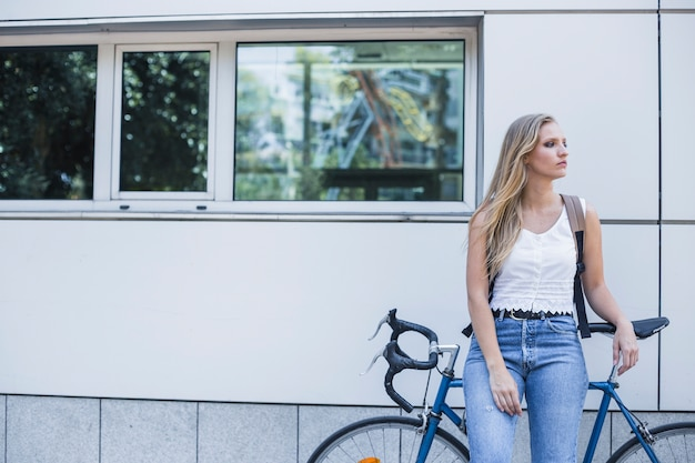 Young woman waiting for someone with bicycle