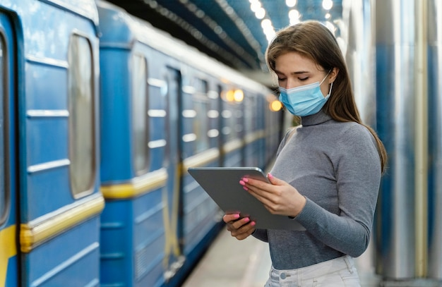 Young woman waiting in a subway station with a tablet