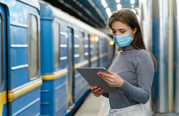 Giovane donna in attesa in una stazione della metropolitana con un tablet