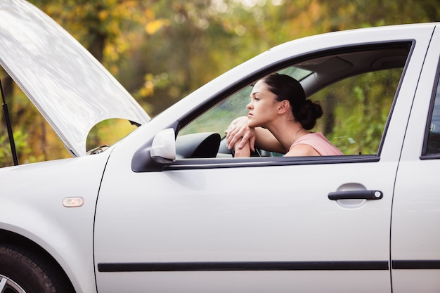 Young woman waits for assistance near her car, which broken down on the road side