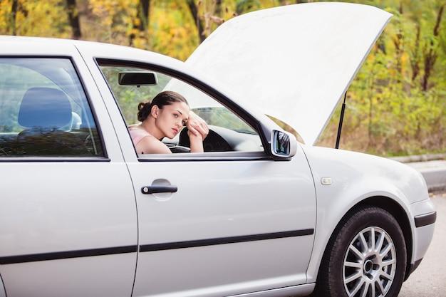 Молодая женщина ждет помощи возле своей машины, которая сломалась на обочине