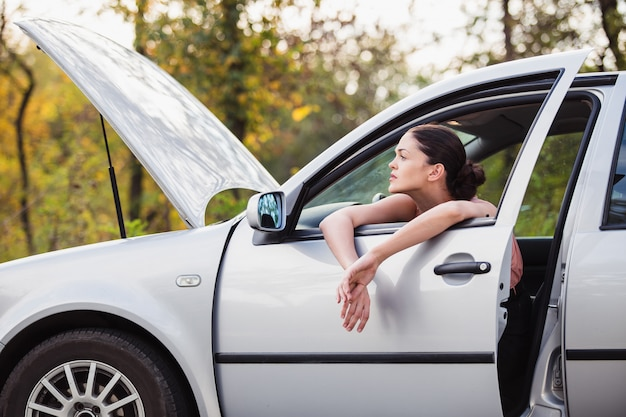 젊은 여자는 길가에서 고장난 그녀의 차 근처에서 도움을 기다립니다.