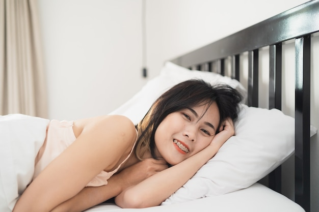 Young woman wake up on the bed in the bedroom at home