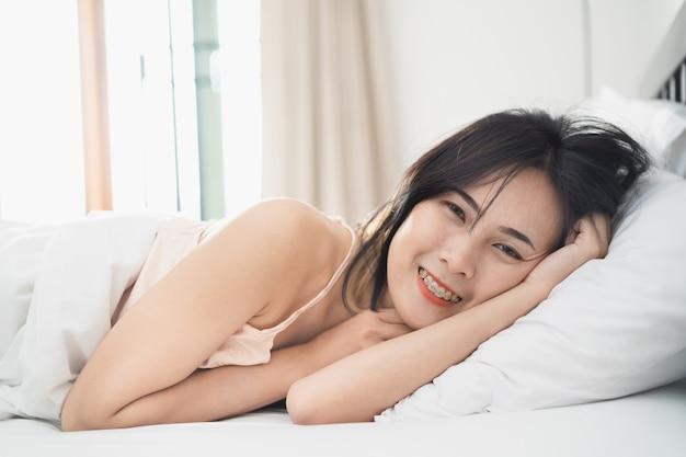 젊은 여자는 집에서 침실에 침대에서 일어나