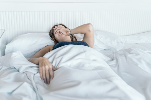 Young woman wakes up in bed with a headache and little desire to start the day.