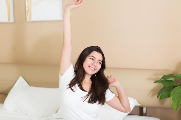 Молодая женщина просыпается и поднимает руки на кровати в спальне отеля