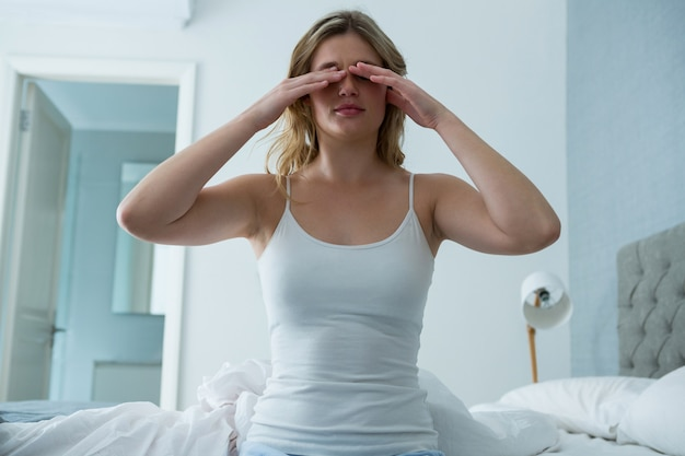 Молодая женщина просыпается от сна в спальне