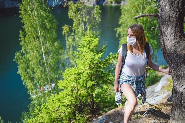 Молодая женщина идет против скалы с зелеными деревьями и синим горным озером в защитной маске для предотвращения covid 19.
