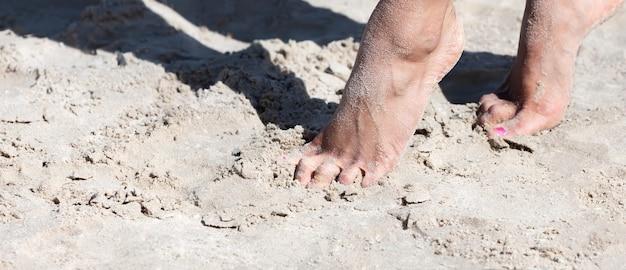 砂浜を歩いている若い女性。海辺の砂の中の女性の足