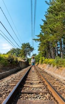 A young woman walking along the train tracks of urdaibai, a bizkaia biosphere reserve next to mundaka. basque country