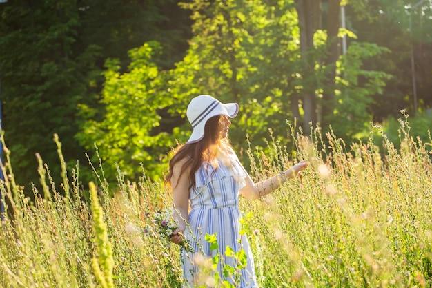 晴れた夏の日に野生の花の間を歩く若い女性とのコミュニケーションの喜びの概念