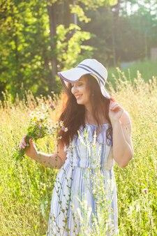 晴れた夏の日に野生の花の間を歩く若い女性