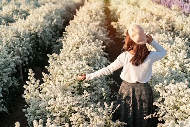 산책 하 고 흰색 개화 꽃 필드에서 즐기는 젊은 여자