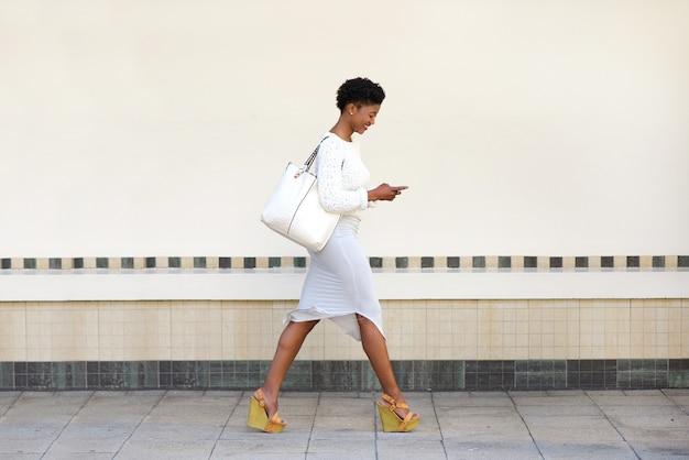 산책 하 고 휴대 전화에 문자 메시지를 보내는 젊은 여자