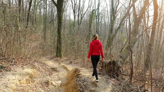 Молодая женщина идет одна по лесной тропе в красном пуховике осенью и зимой