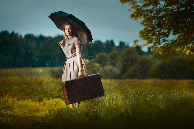 雨の下でスーツケースを持って歩いていく若い女性