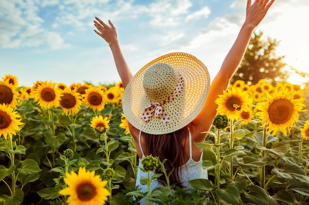 Young woman walking in blooming sunflower field raising hands and having fun.