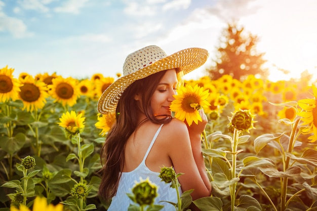 Young woman walking in blooming sunflower field and smelling flowers.