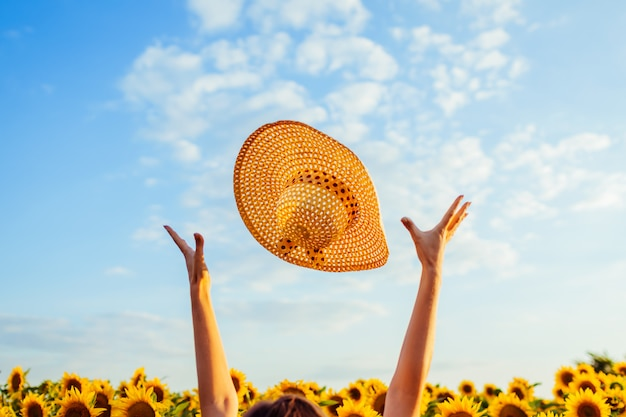 Young woman walking in blooming sunflower field throwing hat up and having fun.