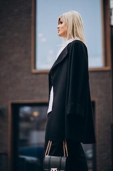 Giovane donna che cammina vicino all'edificio