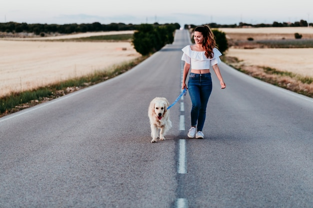 Young woman walking by the road with her golden retriever dog at sunset. pets outdoors