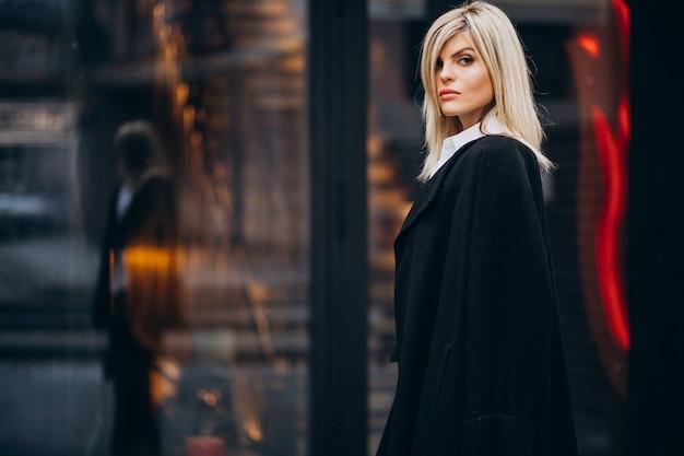 Молодая женщина, идущая мимо здания