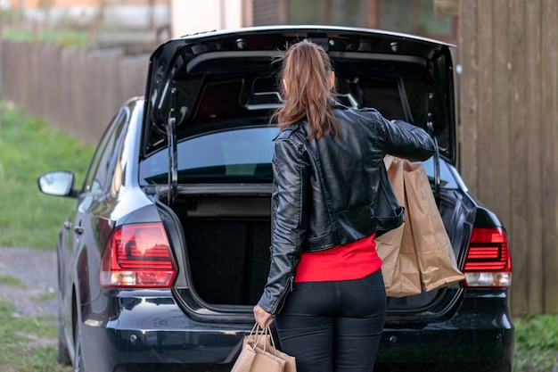 Young woman walking to car with purchases from market
