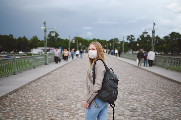 Young  woman walking in city street among the crowd with backpack wearing face protective mask for covid 19 prevention