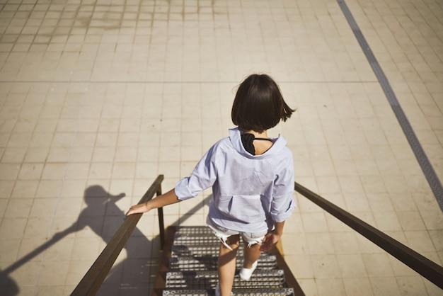 階段を降りて歩く若い女性