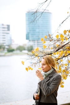 Young woman walking and drinking take away coffee in the city autumn season copy space Premium Photo