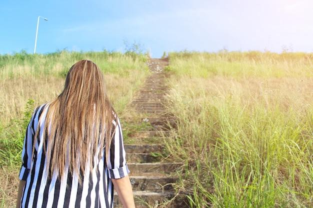 Giovane donna che cammina in campo verso il sole