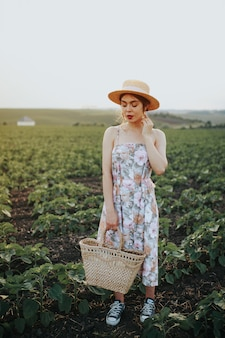 Young woman walking in flower field and high grass wearing hat and dress. vertical portrait at sunset