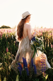 Young woman walking in flower field and high grass wearing hat and dress.