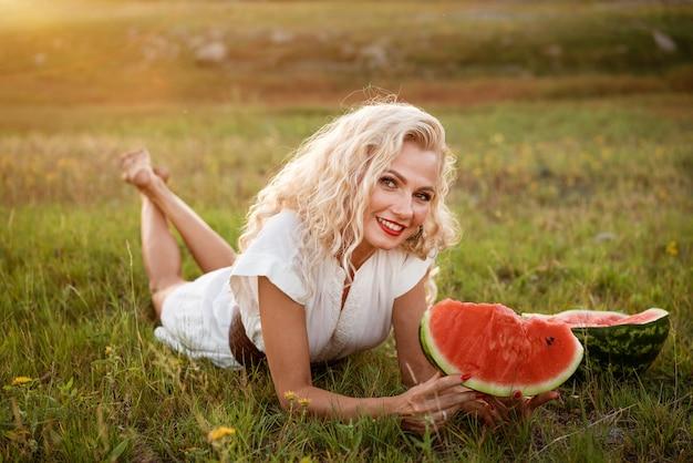 夏を楽しんで夢を見ている晴れた日に屋外の公園を歩いている若い女性