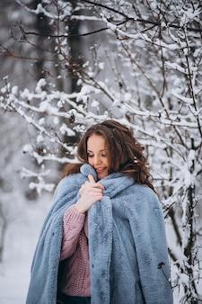 Молодая женщина гуляя в парк зимы