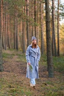 トレンディな都会の服を着て秋の森の少女を歩く若い女性は松林が暖かい日を楽しむのだろうか