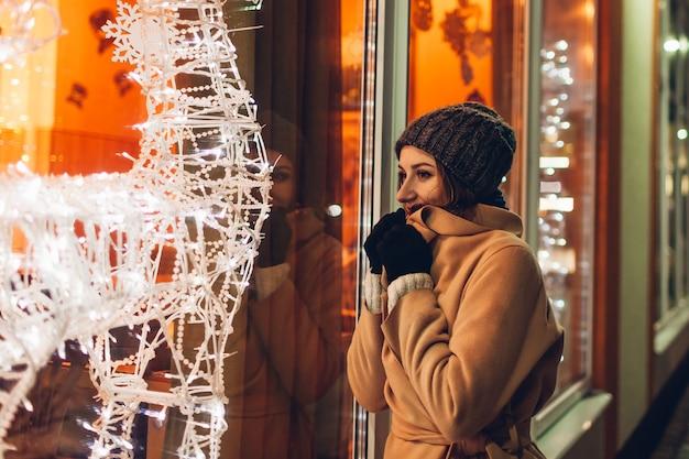 도시를 걷고 밤에 장식된 크리스마스 쇼케이스를 보고 있는 젊은 여성. 새해 개념
