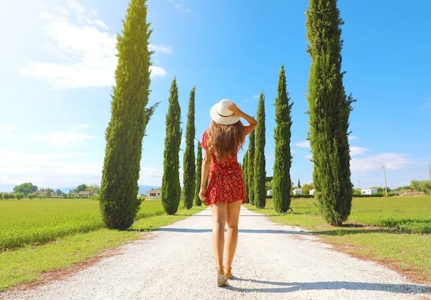 トスカーナのイタリアの田舎の糸杉の車線を歩く若い女性