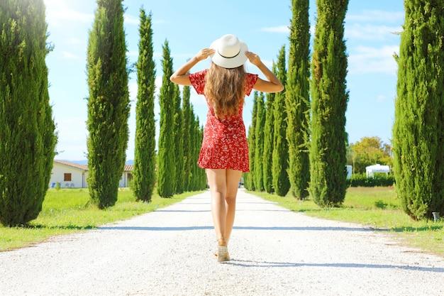 イタリアのトスカーナの田舎で糸杉の車線を歩く若い女性