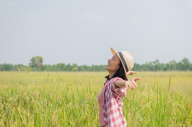 태국에서 쌀 필드에 걷는 젊은 여성. 지구의 깨끗한 곳을 여행하고 자연의 아름다움을 발견합니다. 모자 서와 젊은 여성 여행자입니다.