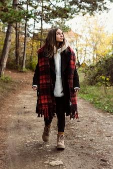 숲에서 산책하는 젊은 여자
