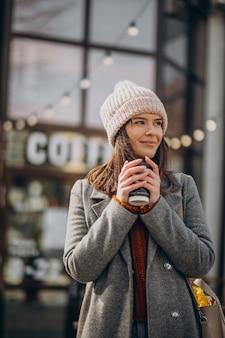 Молодая женщина гуляет по улице и пьет кофе