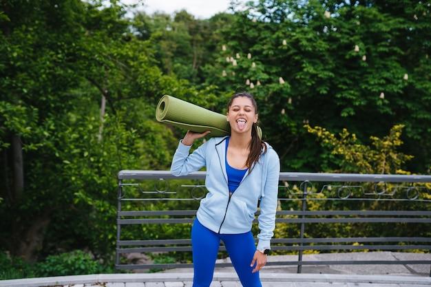 フィットネスラグを保持している都市公園を歩く若い女性。