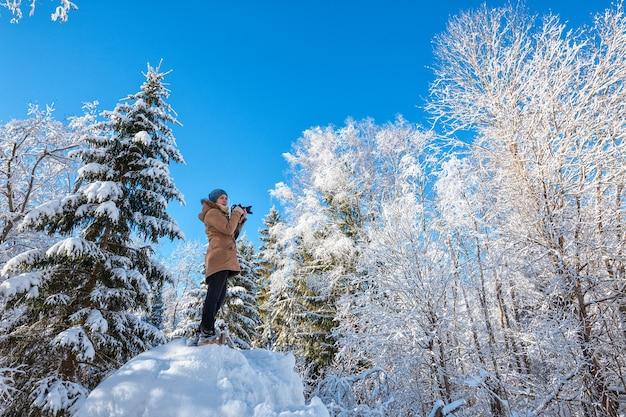 冬の森を歩いて写真を撮る若い女性