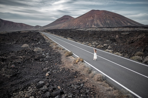 Young woman walking in the middle of a lonely road set in a dark mountain landscape.