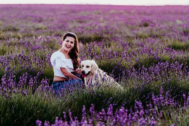 夕暮れ時の彼女のゴールデンレトリーバー犬と紫のラベンダー畑の上を歩く若い女性。屋外のペット